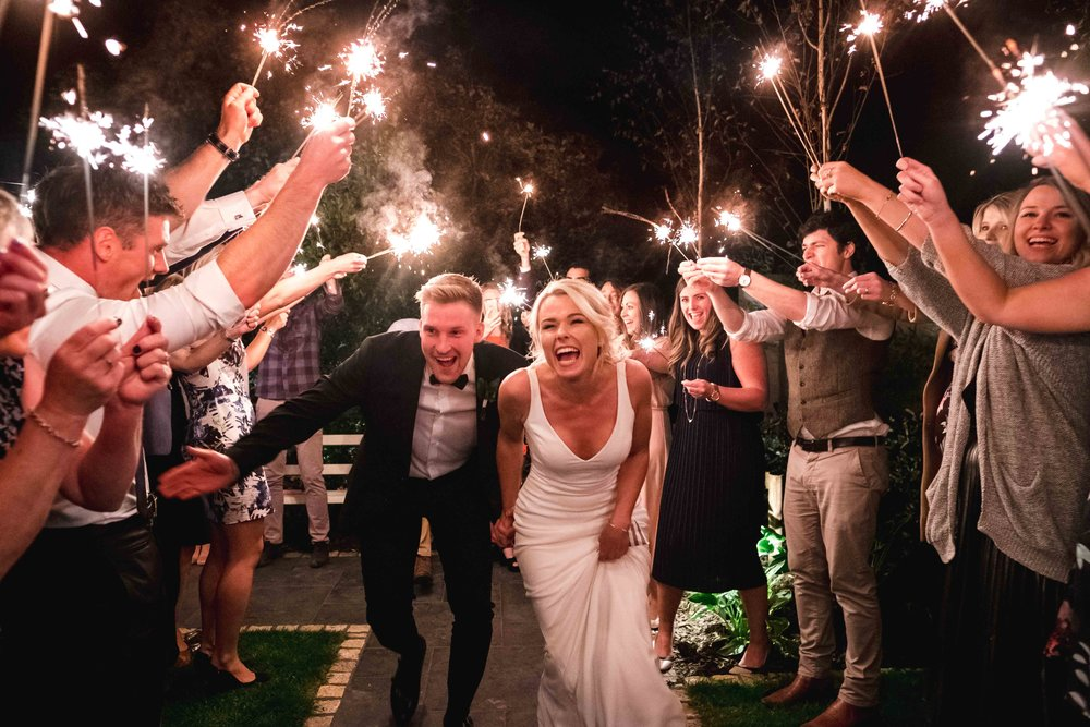 Bride and Groom run through sparklers at the end of their wedding celebrations on the Northern Irish Coast, Portballintrae