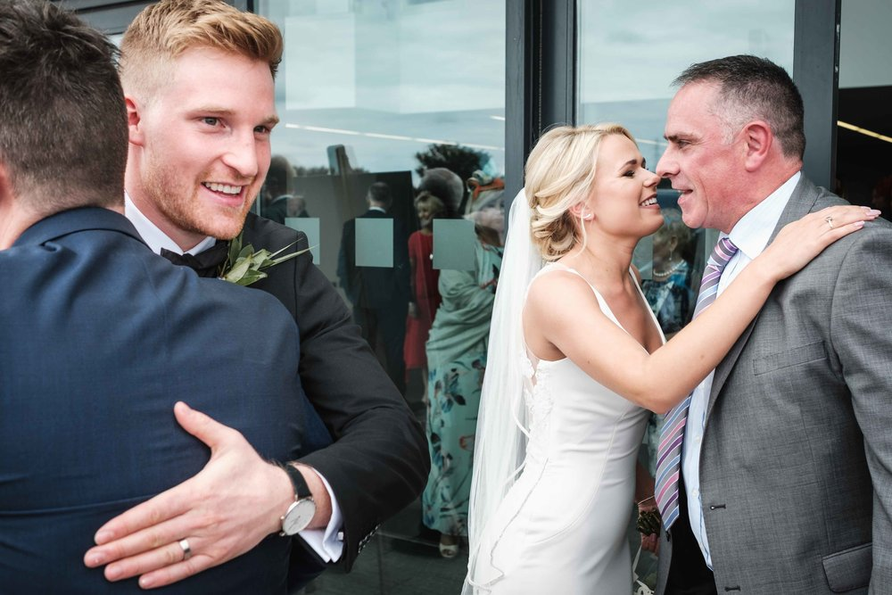 natural photograph of Bride and Groom hugging guests after the wedding ceremony