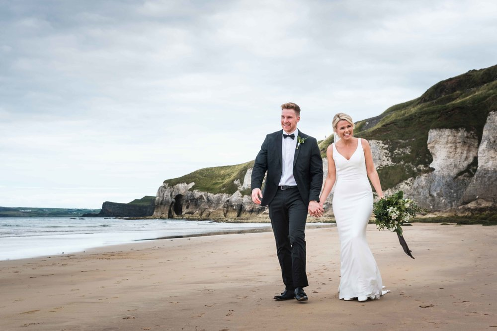 Natural and Relaxed wedding photograph of Bride and Groom walking along the beach on the North Coast of Ireland