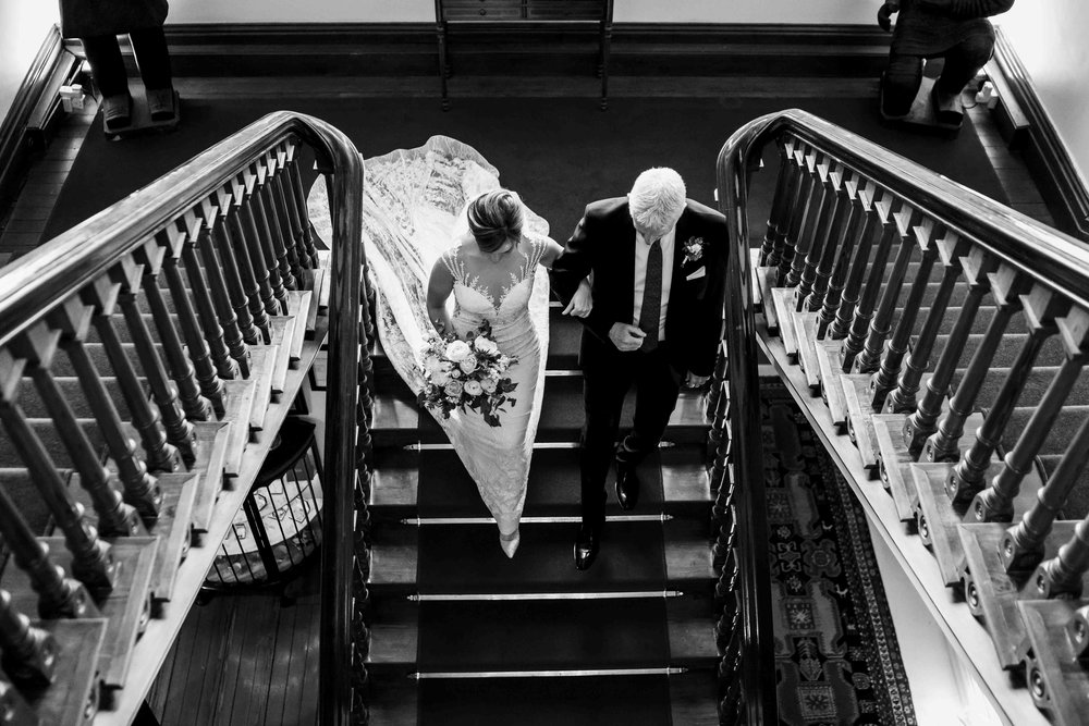 Natural candid wedding photograph of the bride walking down the atirs of Tinakilly House to her wedding ceremony