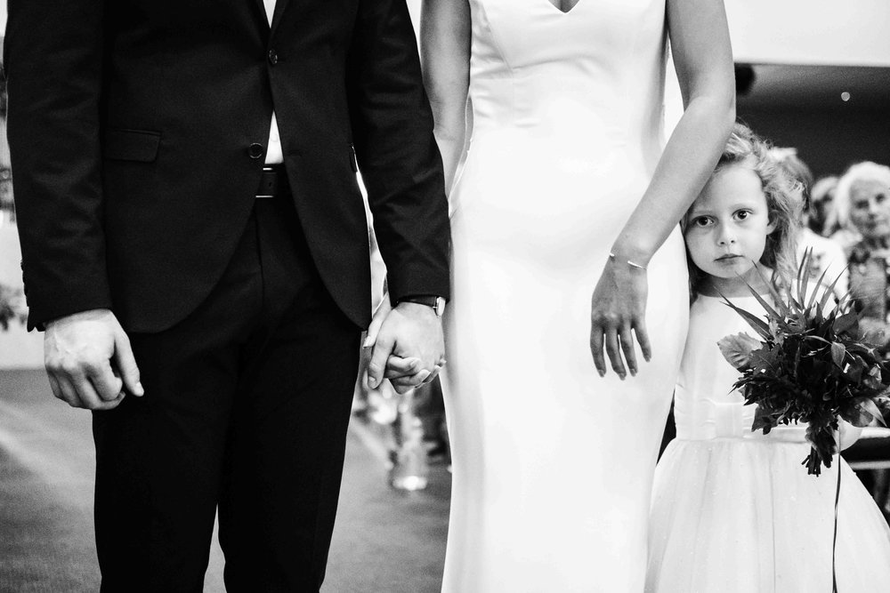 Natural Image of flower girl with bride and groom during Northern Ireland Wedding Ceremony