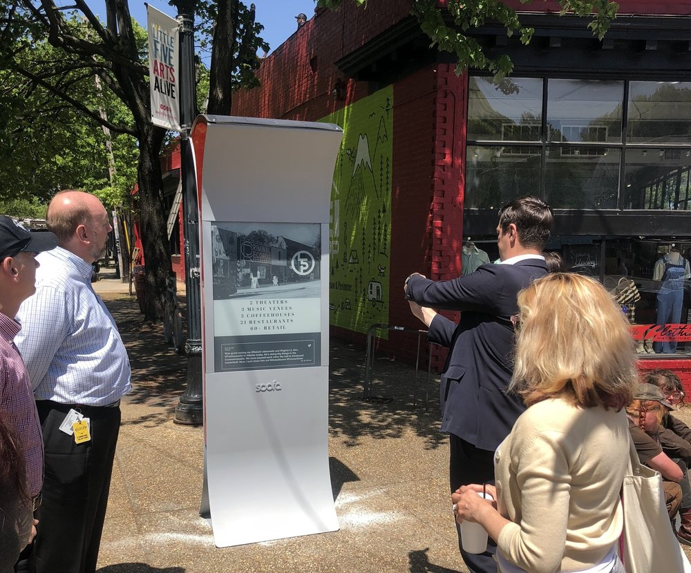 Folks gather around a newly-installed Soofa Sign and snap photos.