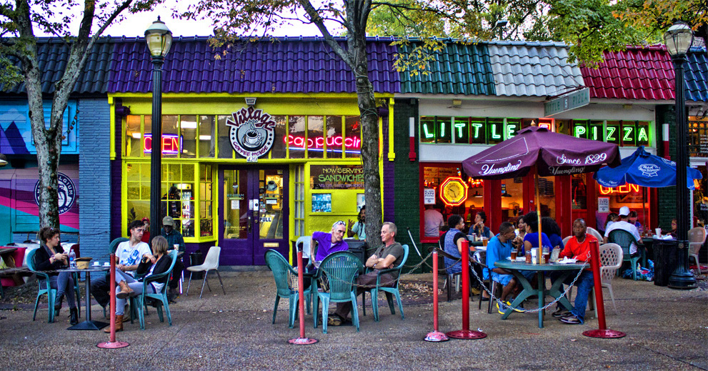People sit at an outdoor patio in the colorful Atlanta neighborhood of Little Five Points.