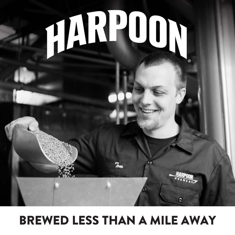 "A Harpoon employee pours grains to be transformed into beer, accompanied by the text: ""Harpoon. Brewed less than a mile away."""