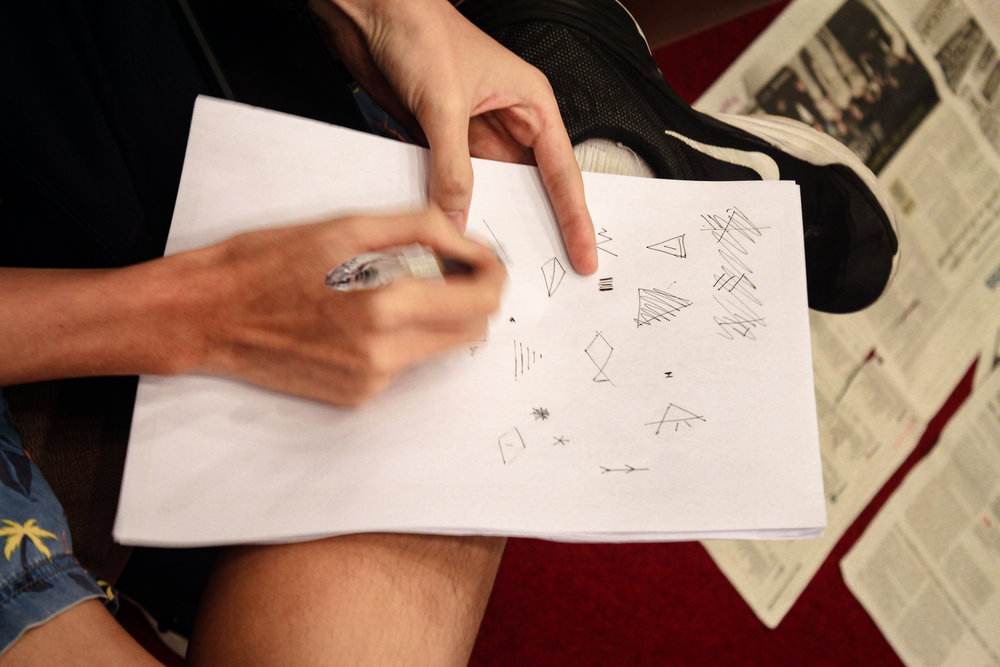 A student engaging in a creativity exercise, where each person had to create as many images as possible using only 5 straight lines
