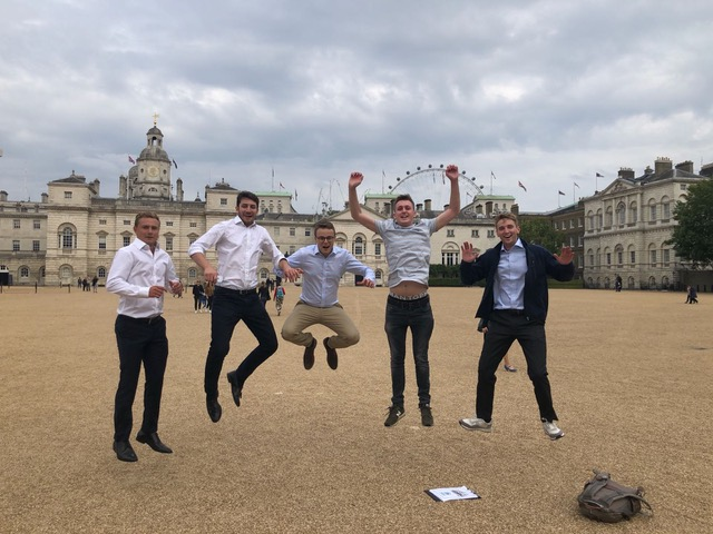 Team all in mid air outside buckingham palace
