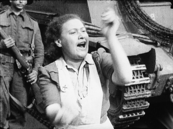 'Ex-prisoner claps her approval of the strictness shown by Tommies.' Still from footage shot by Sergeant Lewis, 16 April 1945.  © Imperial War Museums (FLM 1001).