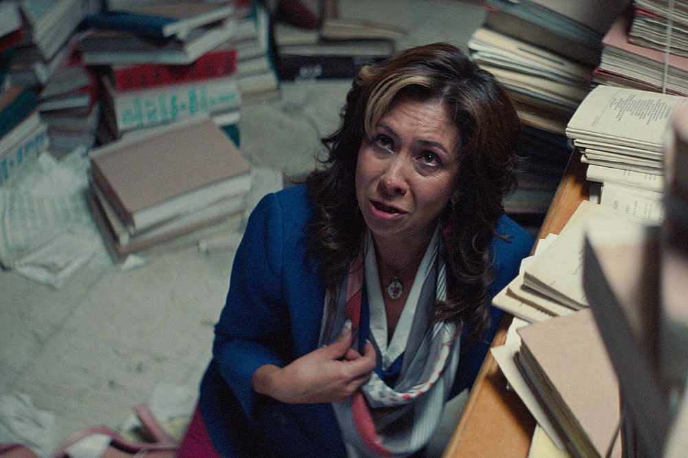 Piles of archived paperwork overwhelm an employee in Joaquín del Paso's Panamerican Machinery.