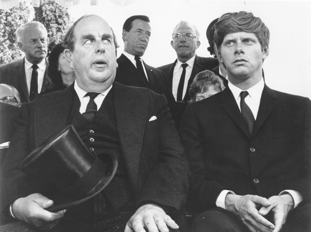 Sir Ambrose Ambercrombie (Robert Morley, left) and Denis Barlow (Robert Morse) at the funeral of former screenwriter Sir Francis Hinsley.