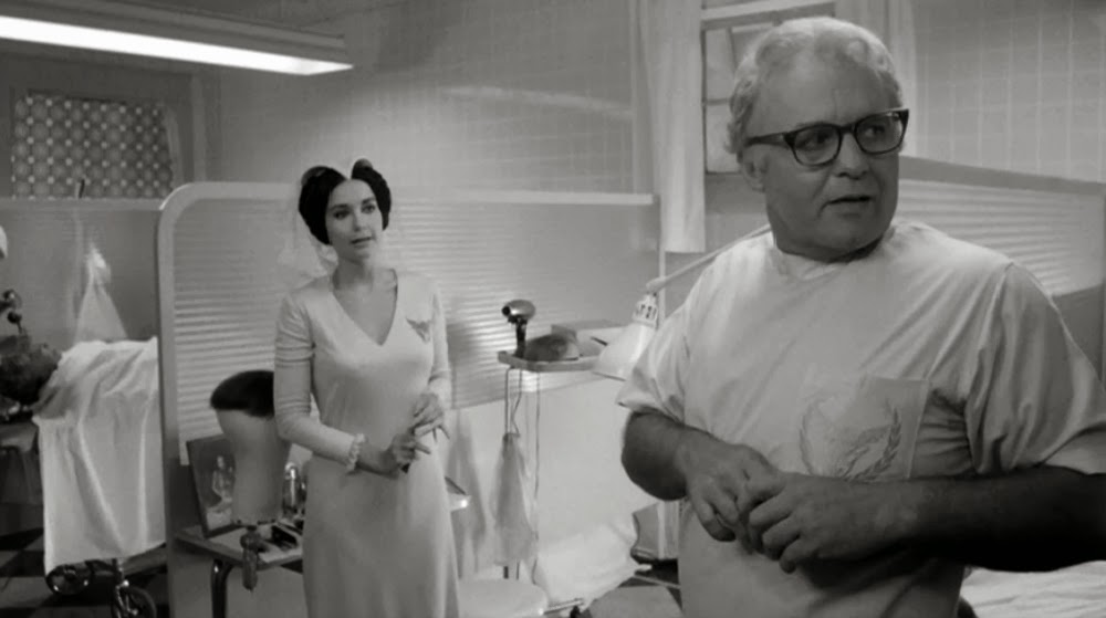 Mr. Joyboy (Rod Steiger) and his assistant Aimée (Anjanette Comer).