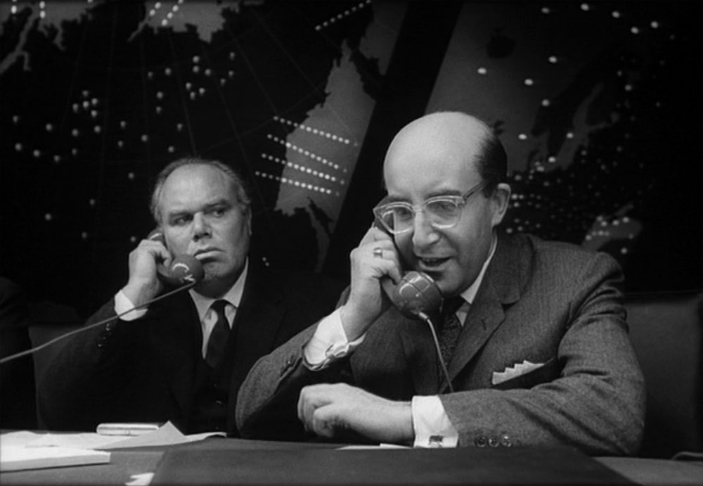 President Muffley (Peter Sellers) on the hotline phone with Premier Kissoff as Russian Ambassador de Sadesky (Peter Bull) listens in. From Stanley Kubrick's dark satire Dr. Strangelove.