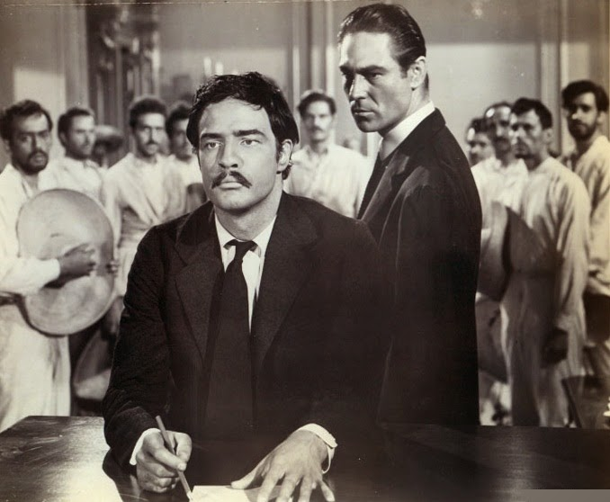 The revolutionary leader Emiliano Zapata (Marlon Brando) recognizes how power corrupts, as  the political opportunist Fernando (Joseph Wiseman) looks on in Elia Kazan's dramatized version of the Mexican Revolution, Viva Zapata!.