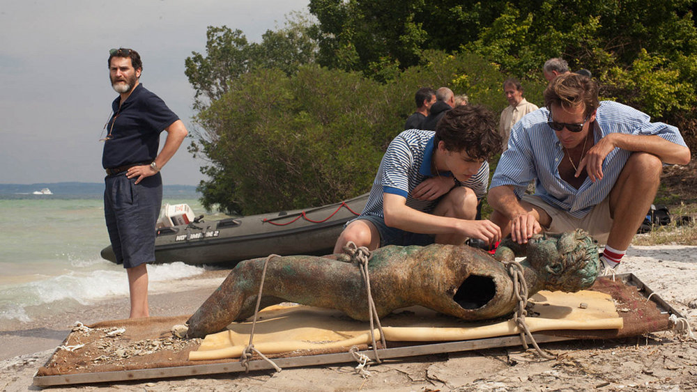 Teenager Elio (Timothée Chalamet, center) and American doctoral student Oliver (Armie Hammer) inspect a Greco-Roman sculpture discovered undersea by Elio's professor father Mr. Perlman (Michael Stuhlbarg).