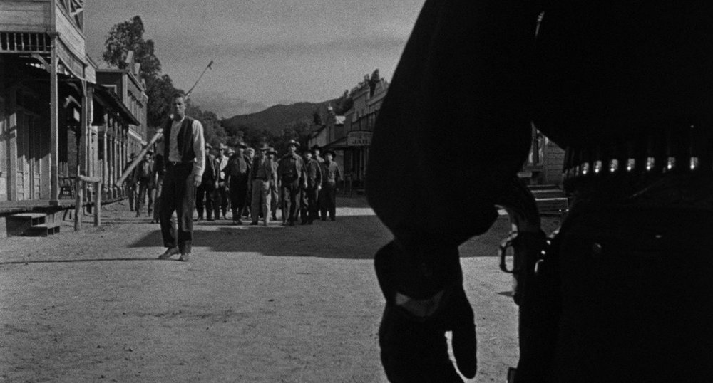 The opening scene features Joseph Lewis's striking framing of an unusual Western showdown.