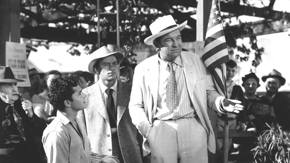 Jack Burden the reporter discovers Stark making a heartfelt if stumbling speech in Kanoma City. Stark's adopted son Tom (John Derek) is on the left.