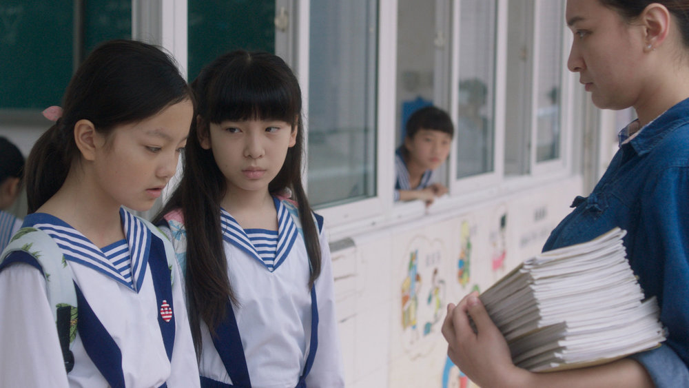 Wen (Meijun Zhou, left) and Xin (Xinyue Jiang) chastised by their teacher for being late for school after a fateful night.