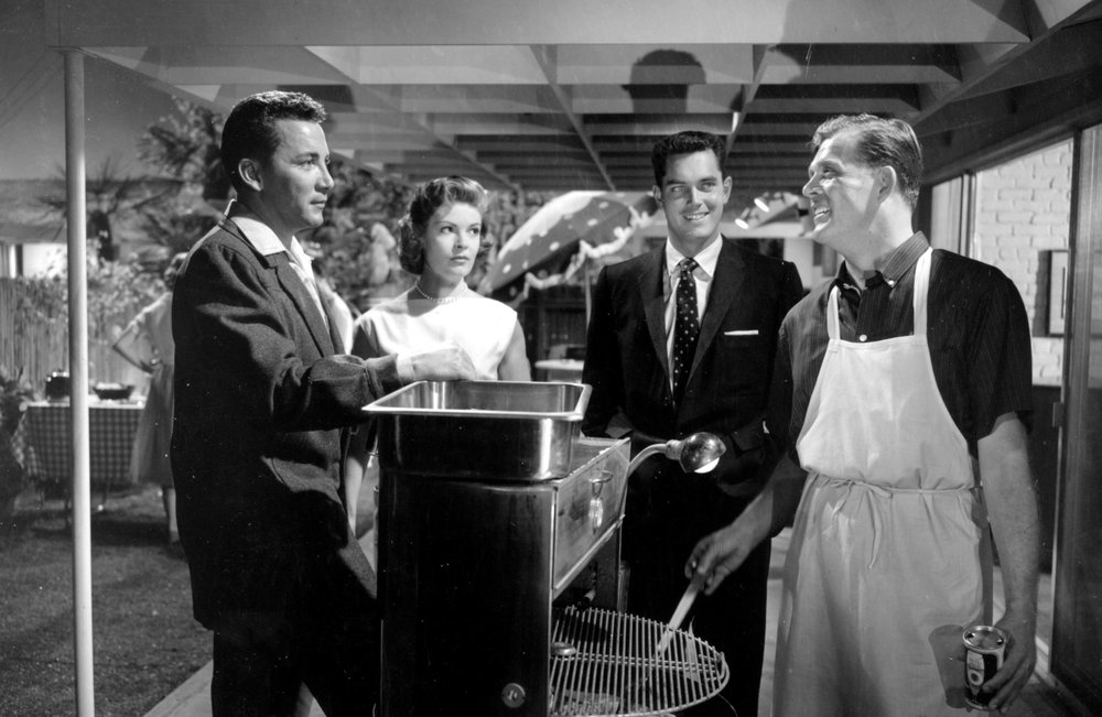 Newcomers in town meet their neighbors at a backyard barbecue hosted by the affable householder (Pat Hingle) behind the grill.