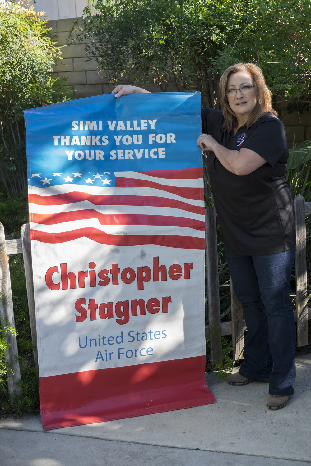 Mardu Lydick, Ventura County Chapter Director of Pets For Vets, holds the banner  displayed in Simi Valley during Christopher's deployment.
