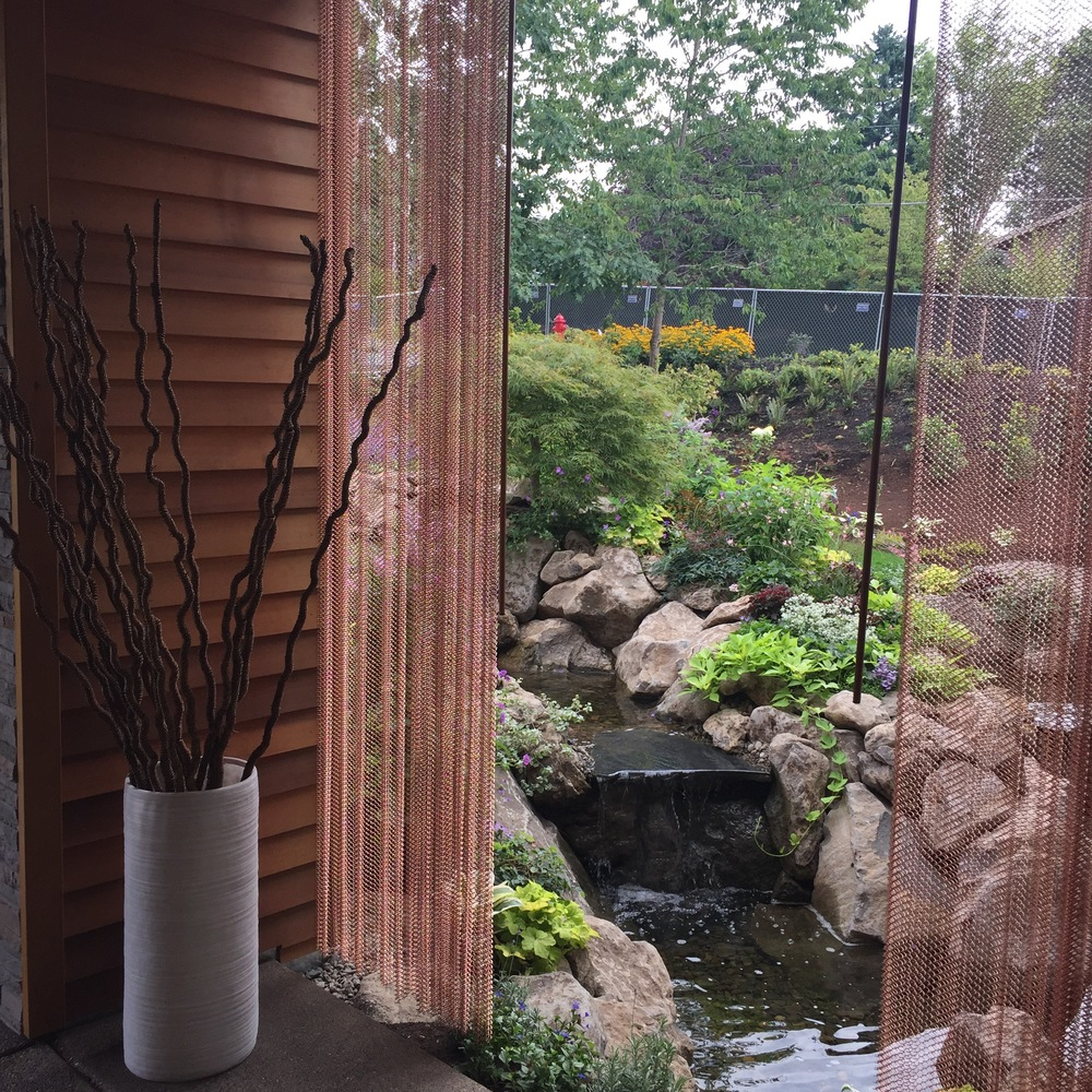 A covered patio with copper-chain drapes overlooked the outdoor pond.