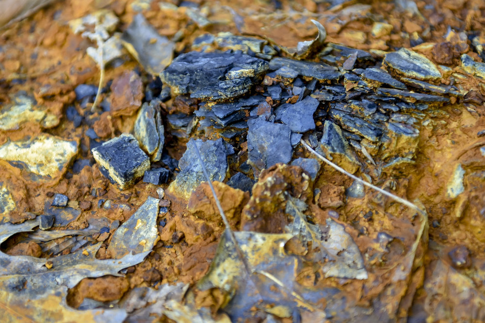 Exposed coal lies in the orange mud outside of the Majestic Mine opening in Nelsonville.