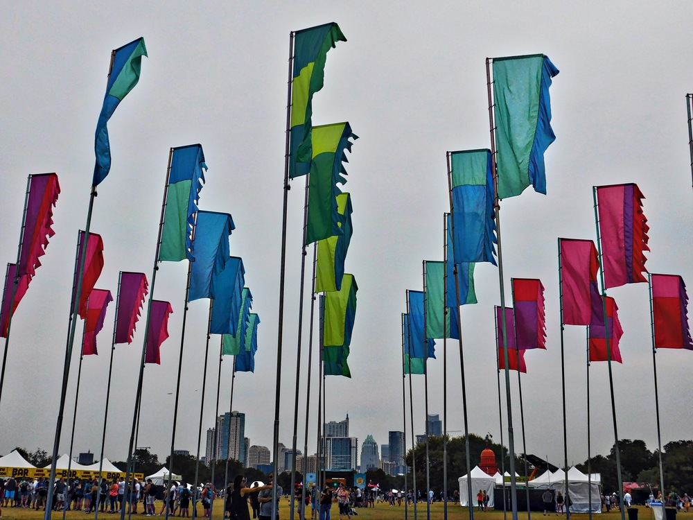 """Flags are a big part of ACL. Here a closeup of the flag """"farm"""" in the middle of the lawn."""