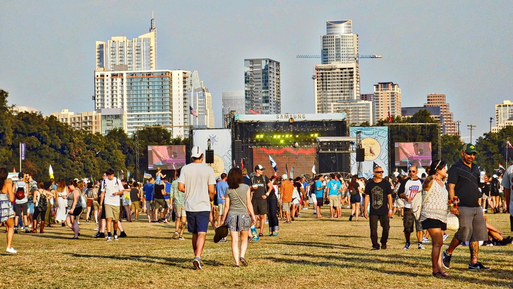 People streaming in to Zilker Park and heading for the main stage with the Austin skyline in the background.