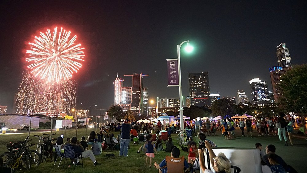 The crowd enjoying July 4th fireworks next to The Long Center.