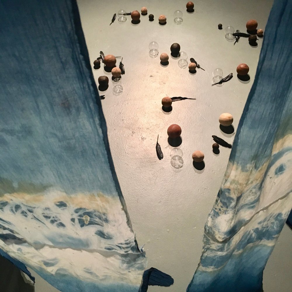Incantation put to the parliament of crows,    2017, installation image.   Turned ecofuel logs, salvaged timber, glass, cyanotype and indigo on cotton, feathers.Soundscape by Peter Houtmeyers.Dimensions variable