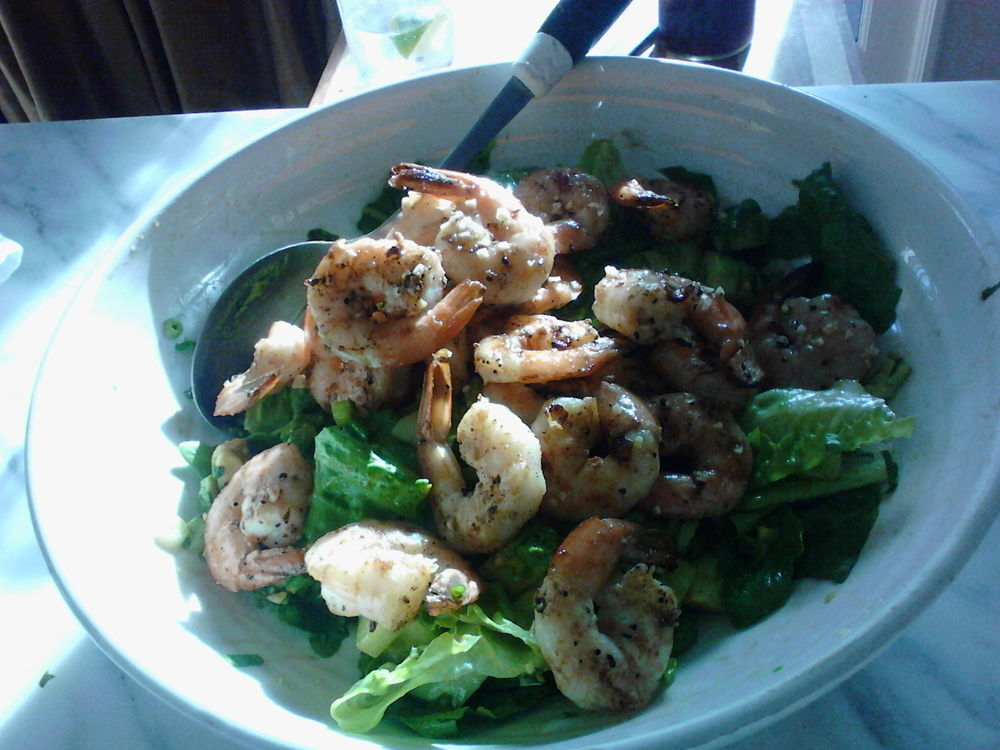Grill the prawns, throw them in the fridge with lime juice, olive oil and garlic.  Make the salad and toss an hour later.