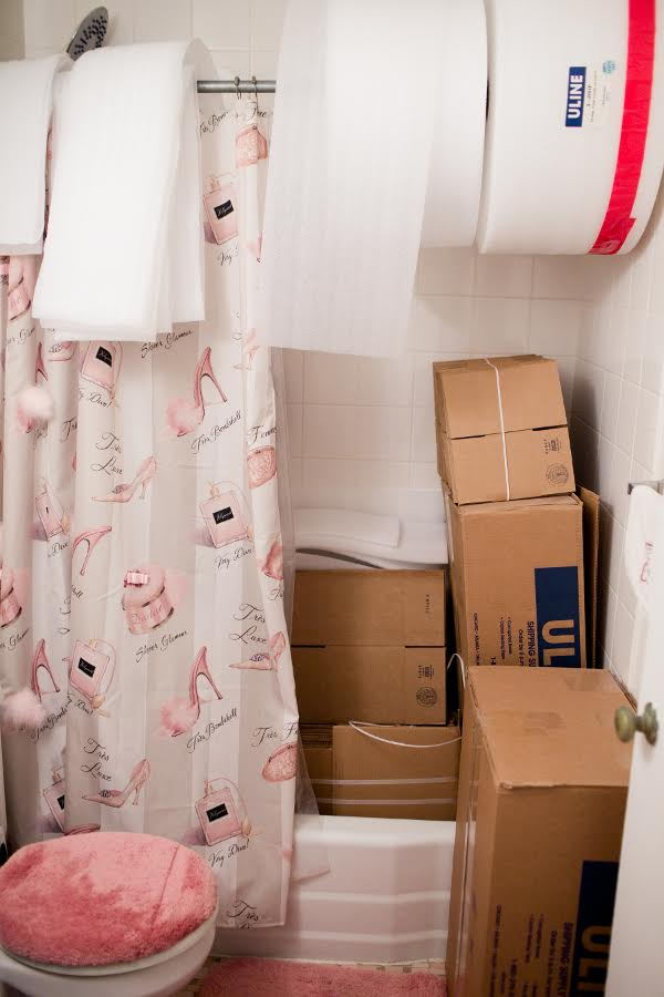 Spare bathroom used for storing large boxes and the shower rod is ideal for large rolls of foam!