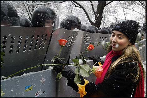 A protester in Kiev inserts roses into riot police shields.