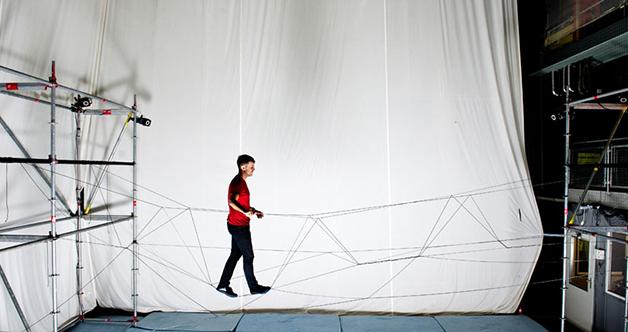 Un estudiante de la Universidad de Zurich prueba una pasarela de cuerda construida con drones