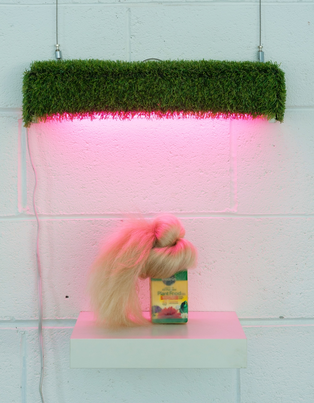 """It's a Miracle! Blonde."" Miracel grow, synthetic hair, beeswax, damar resin, astroturf, fluorescent light 12"" x 10"" x 2.5"""
