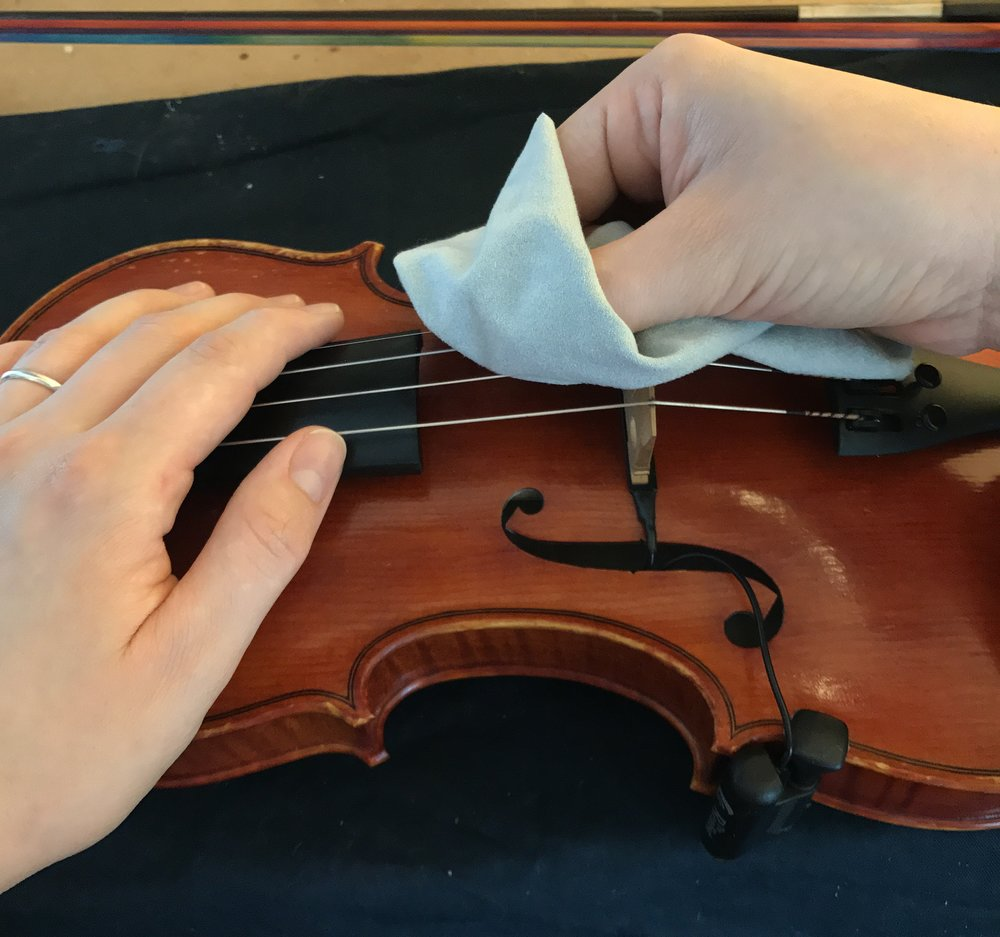 Pinch the strings using the cloth and try to get the excess rosin and dirt off your strings. -