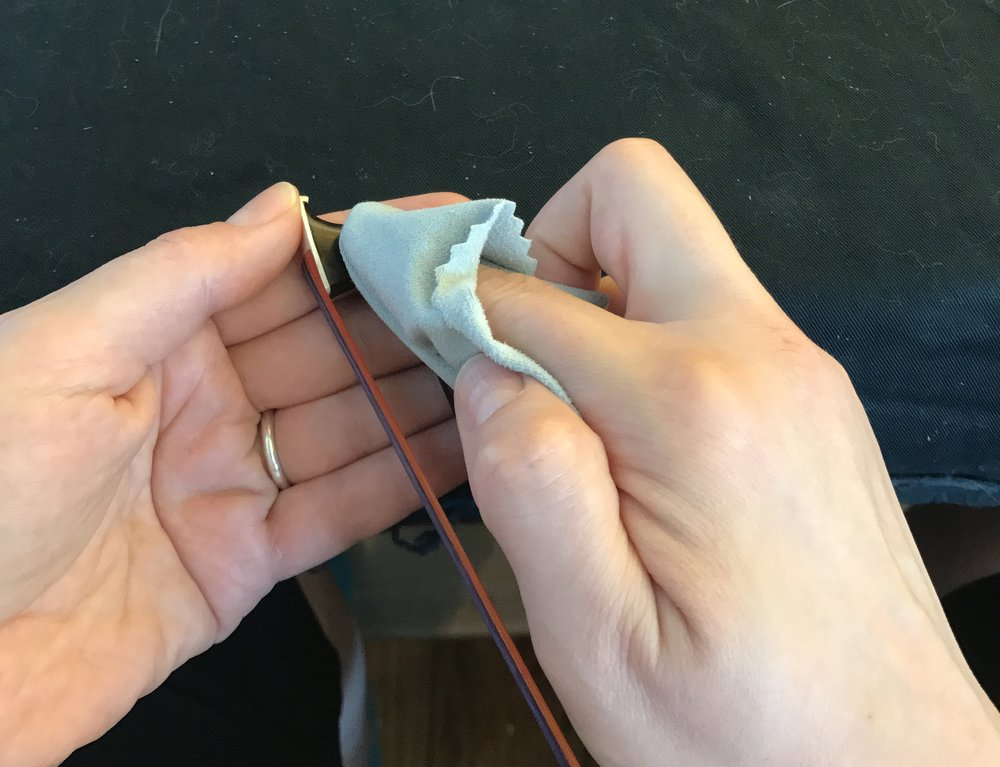 Wipe off rosin to the head of the bow. - Support the head of the bow and gently wipe.
