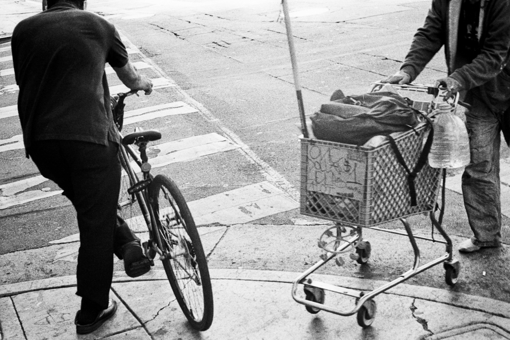 A bicycle and a shopping cart are juxtaposed on the corner of 5th and Los Angles in DTLA