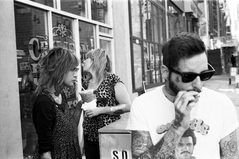 Two women and a man smoke outside of Crimson Unicorn Tattoo on the corner of 5th and Los Angeles in DTLA