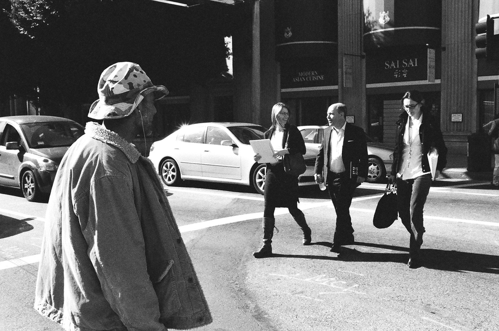 A homeless man approaches businessmen as he crosses the street on 5th and Hill in DTLA