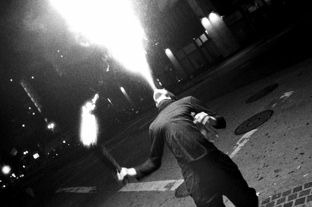 A man breathes fire outside of the Down and Out bar on the corner of 5th and Spring in DTLA