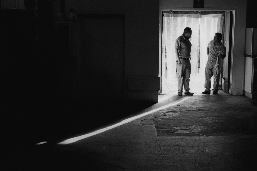 Two employees of the Grand Central Market stand in a doorway