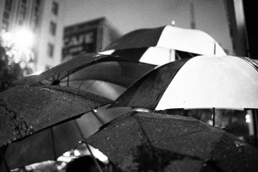 Patrons of Spring Street Bar huddle beneath umbrellas as they smoke cigarettes