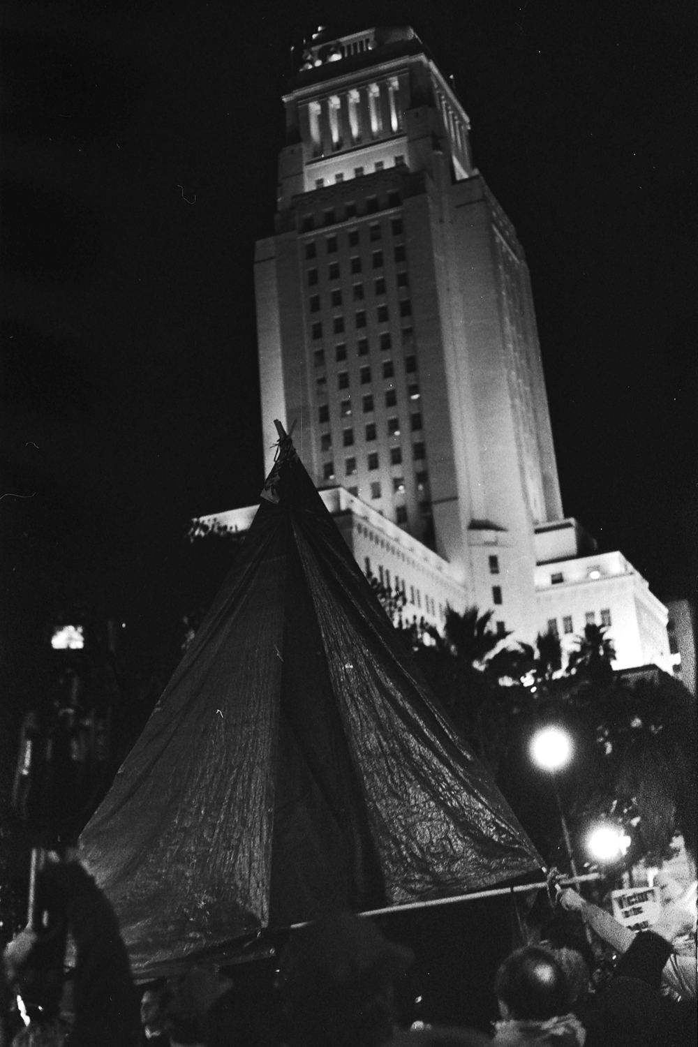 A makeshift tent in the foreground with Los Angeles City Hall in the background during the Occupy L.A. eviction in DTLA