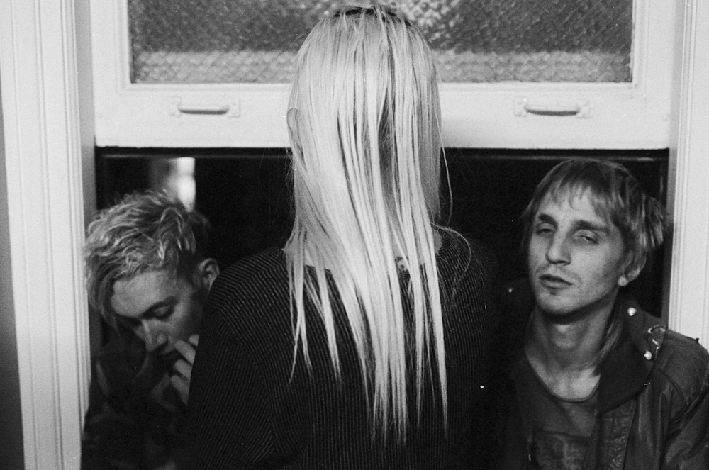 Three party goers stand in front of a hallway window at the Rosslyn Lofts in DTLA