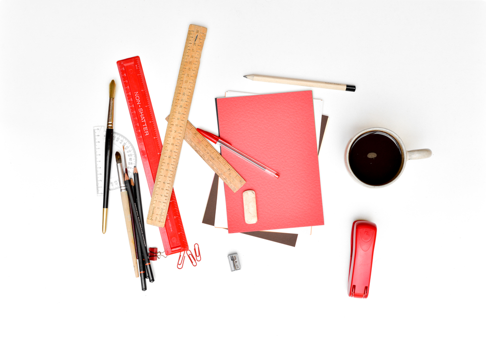 Messy Assorted Stationary On White Desk And Coffee