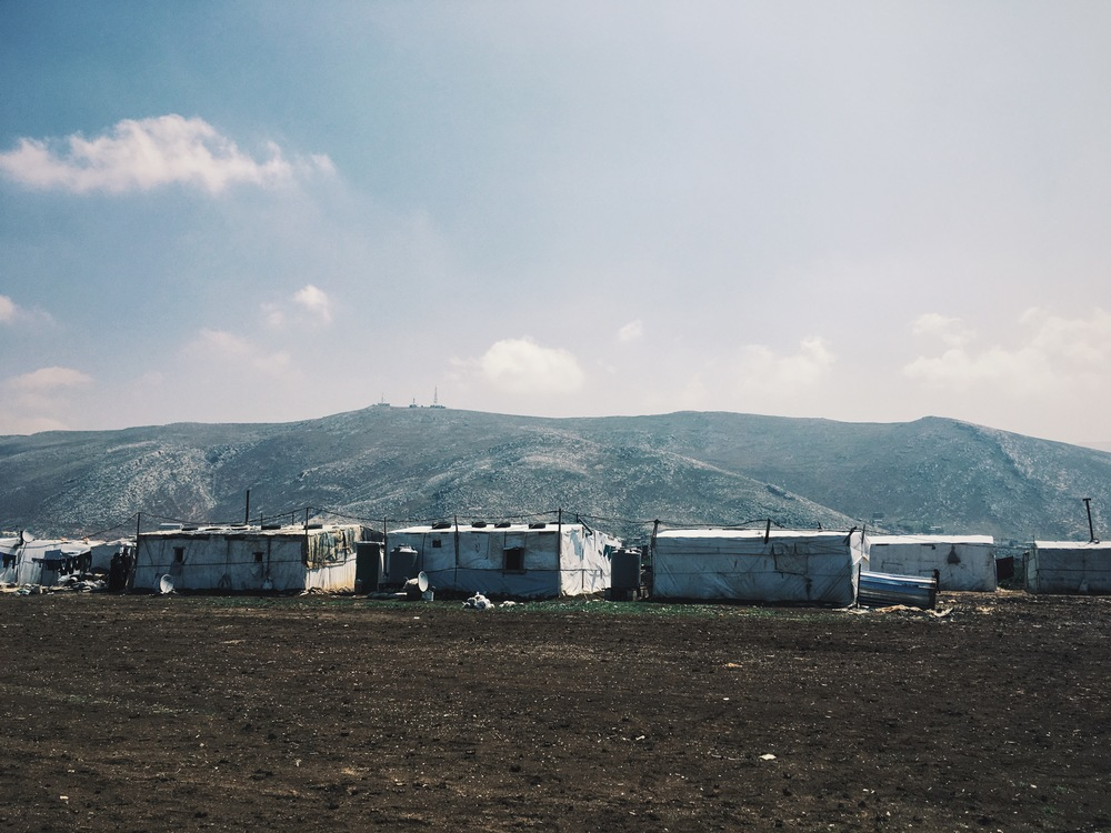 The mountains of Syria form a backdrop to the 'no mans land' of an Informal tent settlement in the Beqaa Valley, Lebanon, March 2016.