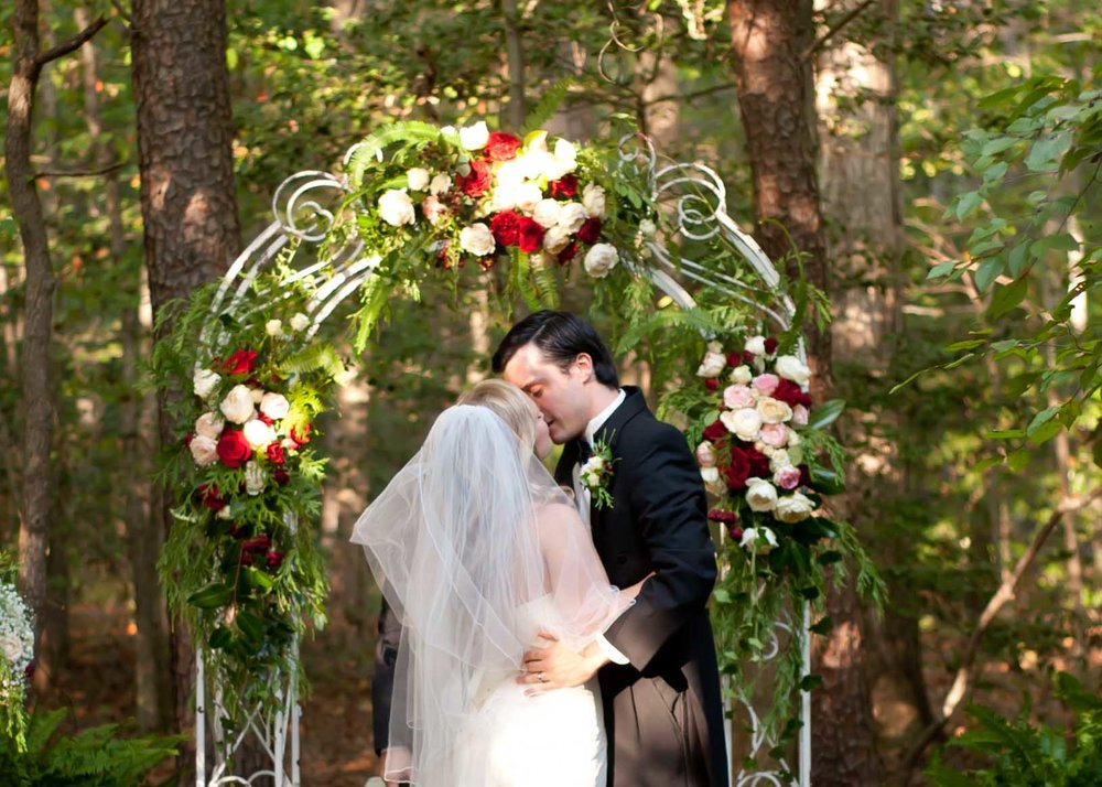 wedding ceremony first kiss bride groom ceremony alter florals .jpg