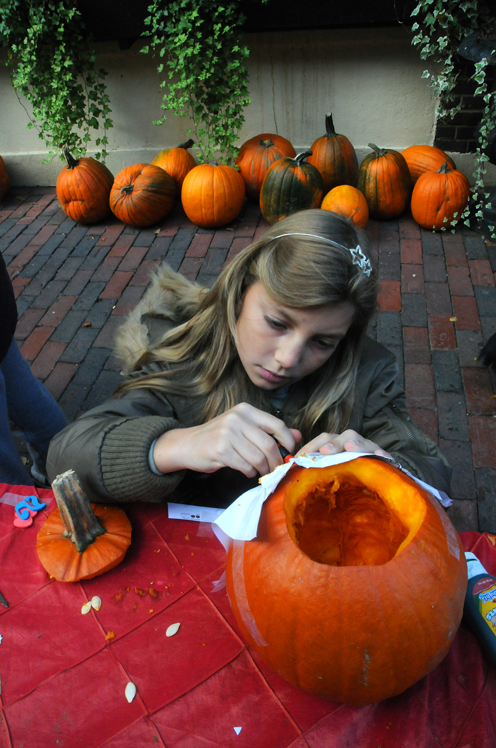 A girl carving a pumpkin at a Halloween event in Boston's North End.