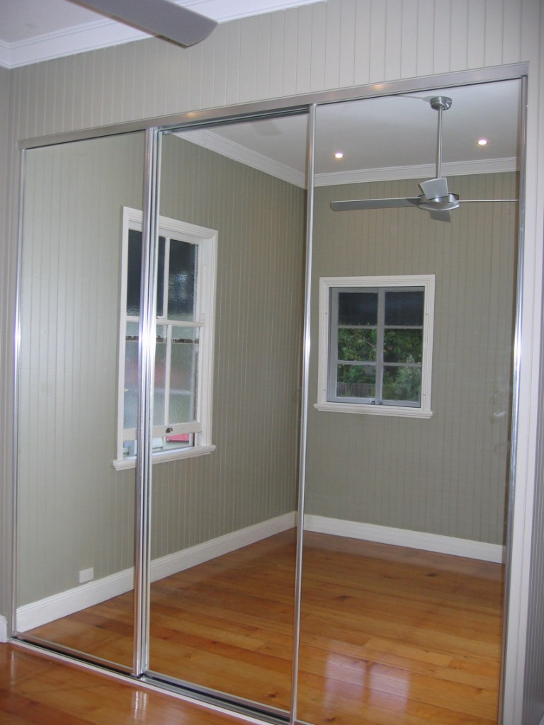 Wardrobe with mirrored sliding doors and matt chrome tracks and door frames