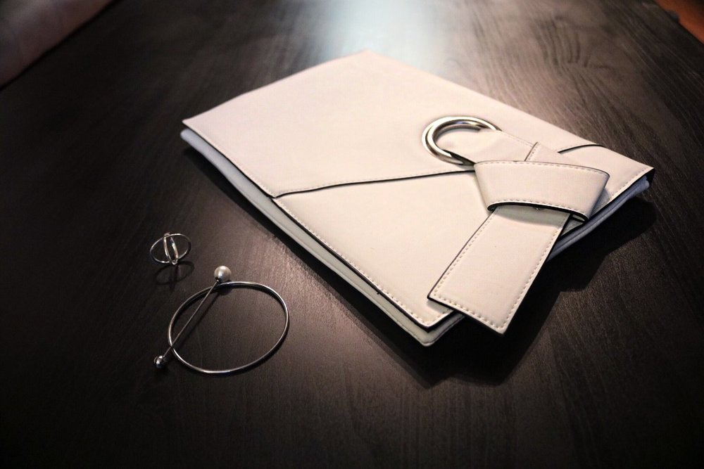 silver minimal cross ring and bracelt and white clutch
