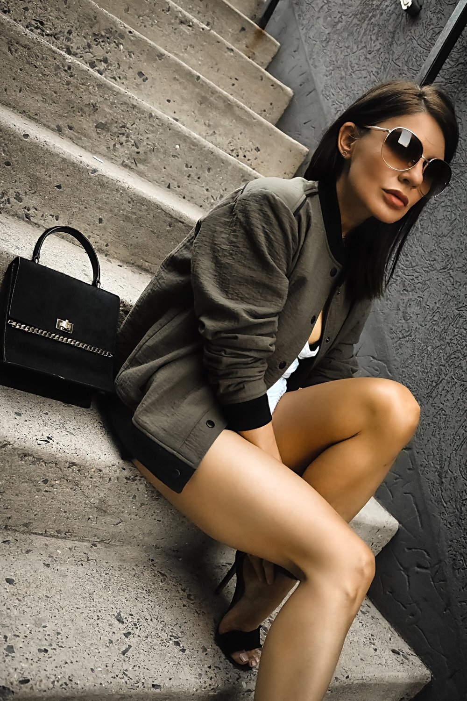 Isabel Alexander Wearing Alala Olive Bomber Jacket Sitting Down Pavement